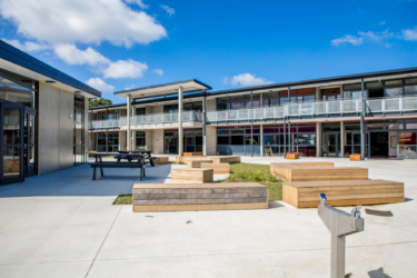 Koru school shown on a sunny day, a courtyard is shown in the foreground with two rows of classrooms in the background