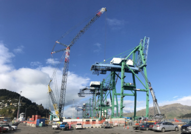 Industrial port cranes are show on a sunny day with machinery and shipping containers in the foreground.