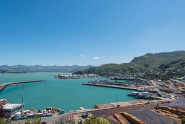 Bright landscape image of Lyttleton harbour, various parts of the port are visible in the foreground