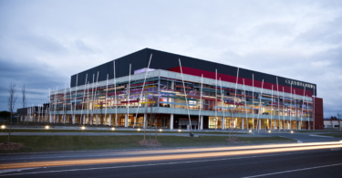 Events centre pictured at dusk with dramatic feature lighting and stylised light from passing road traffic