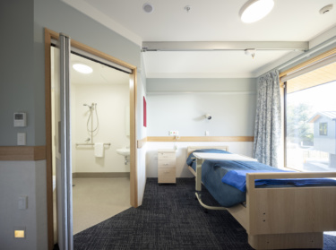 An interior shot of a room showing a bed and an ensuite with facilities for disabled persons