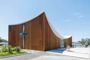 Pictured on a sunny day the building, clad completely in natural cedar, features a dominating concave roofline.