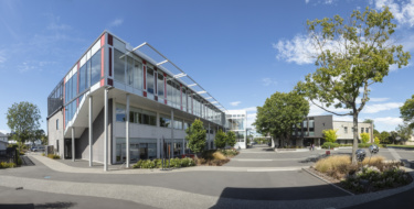 A panorama of the campus courtyard surrounded by glass fronted two story buildings.