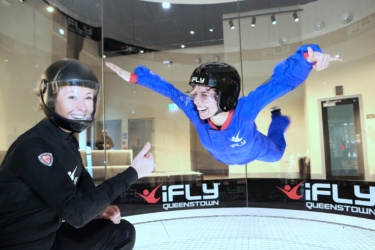 Instructor smiles and gives 'thumbs up' as another smiling woman floats in the wind tunnel