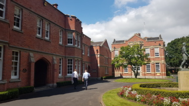 Two men stroll through the quadrangle of kings school beside two-storey gothic revival style bulidings finished in red brick